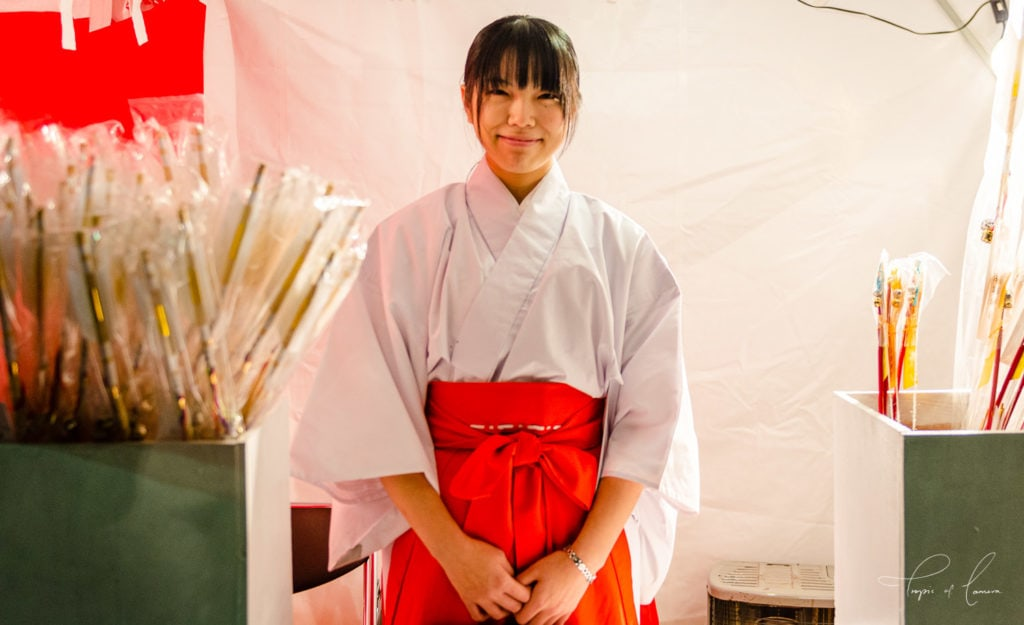 Woman at stall at Senso-ji Temple for New Year celebrations in Tokyo, Japan