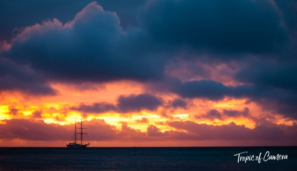 Sailing boat against a dramatic sunset in Fiji