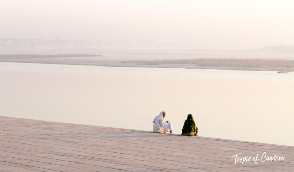 Two people sitting by the river at dawn in Varanasi
