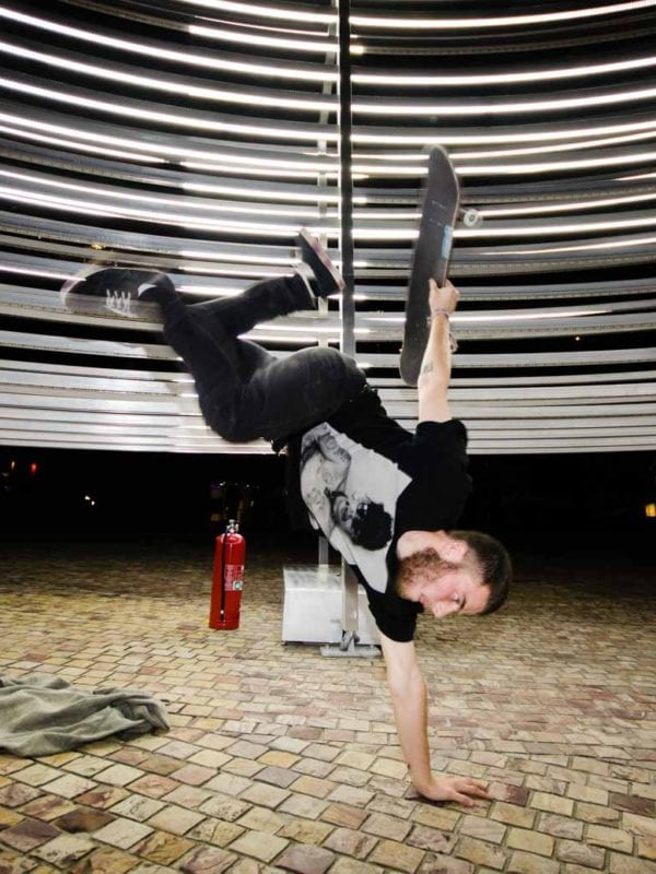 Skateboarder performing against an artwork in Melbourne
