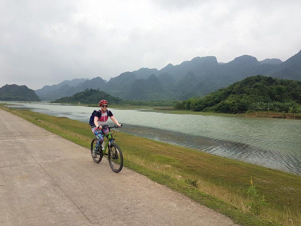 Woman cycling along the road in Ninh Binh, Vietnam