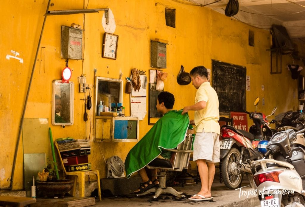Young boy getting a haircut on the street in Hanoi
