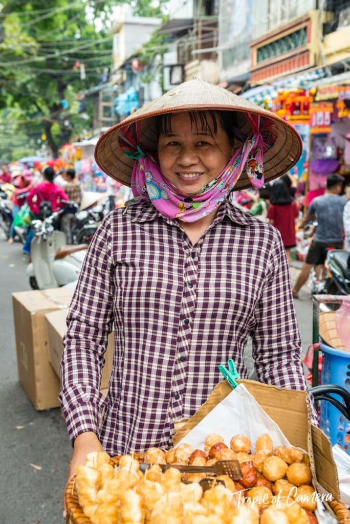 A woman selling donuts on the street at a festival in Hanoi