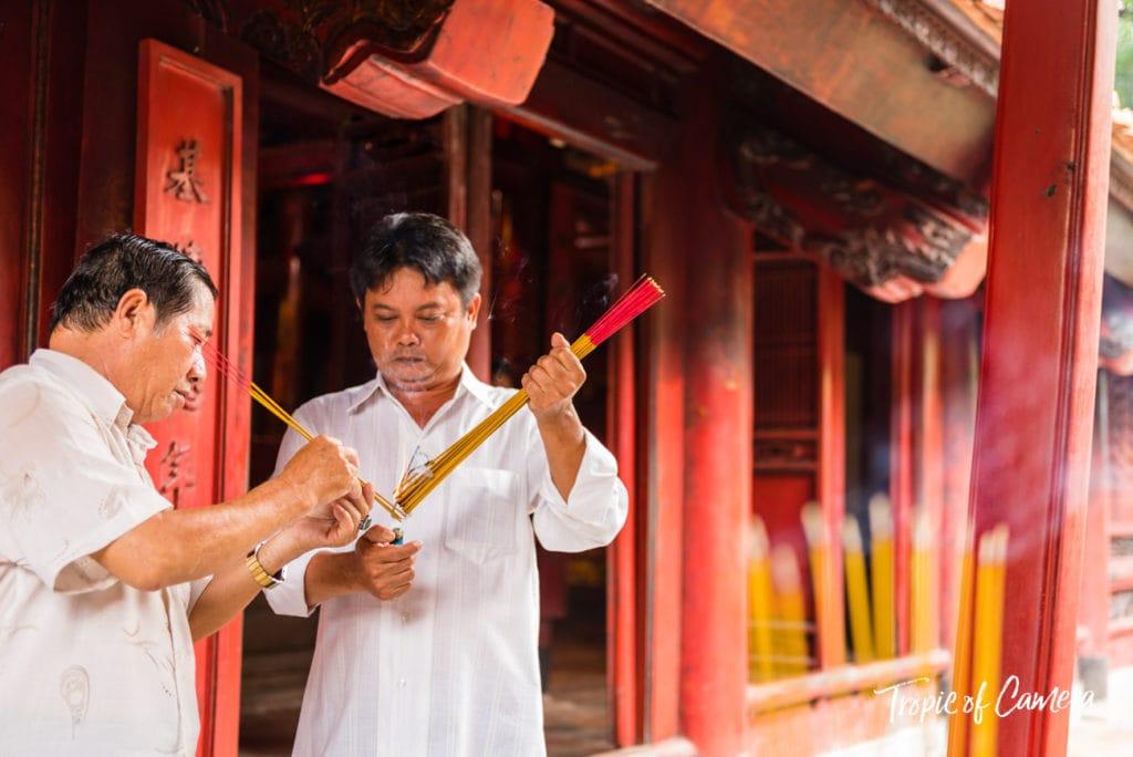 Men light incense sticks at the Temple of Literature in Hanoi