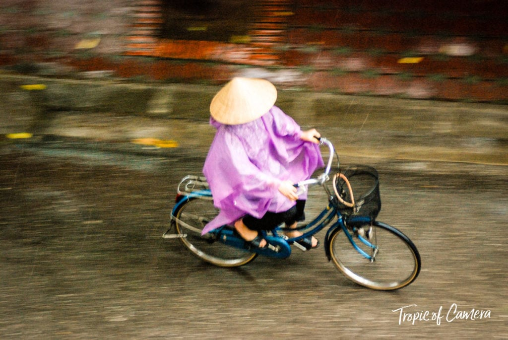 Woman riding bike in the rain in Hanoi, Vietnam