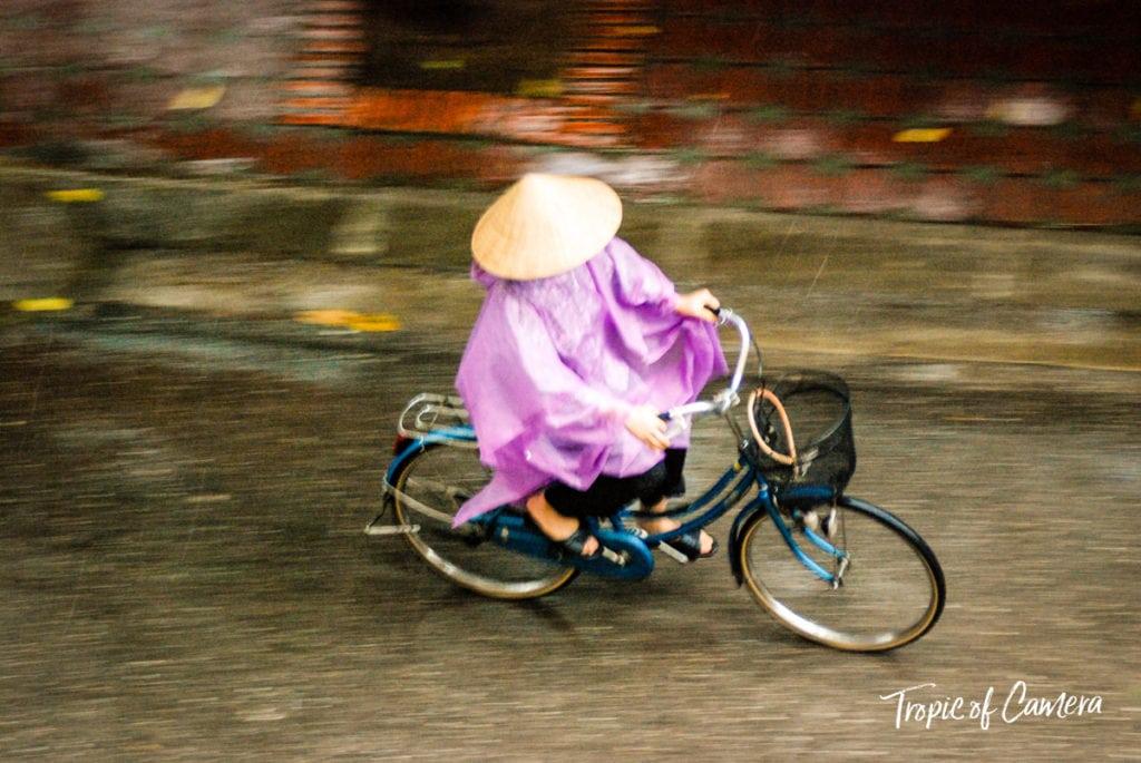 Woman riding bike in the rain in Hanoi, Vietnam