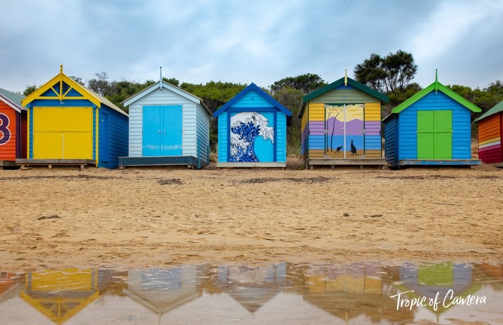 Photograph of Brighton Bathing Boxes reflected in water on a cloudy day