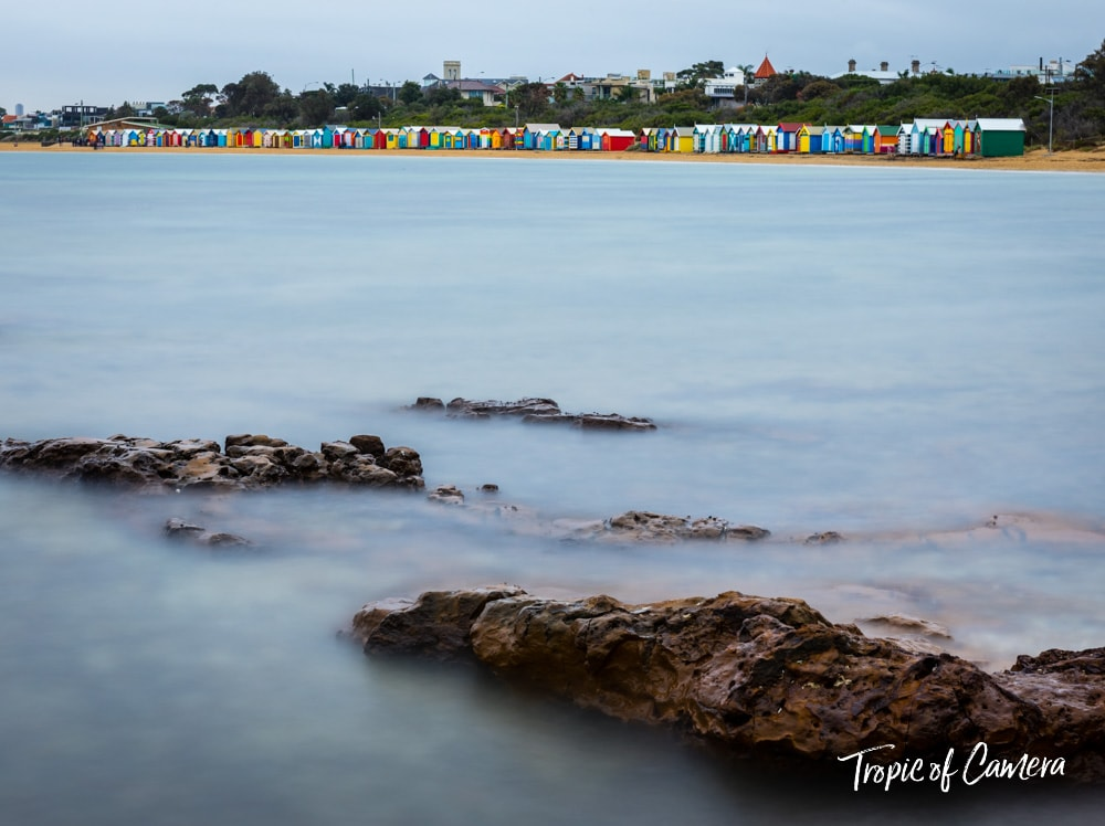 Long exposure photograph of rocks in front of Brighton Bathing Boxes with Melbourne skyline in background