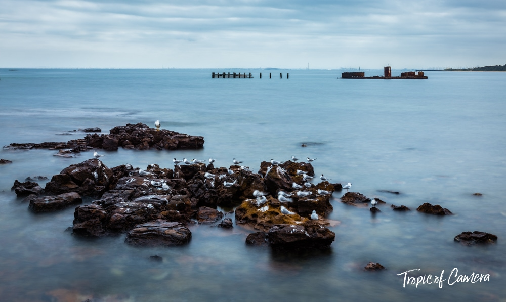 Long exposure photograph of rocks at Half Moon Bay with the shipwreck of HMVS Cerberus
