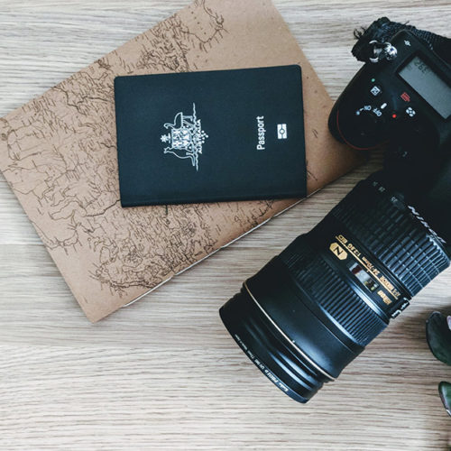 Flat lay of a camera, passport and travel journal