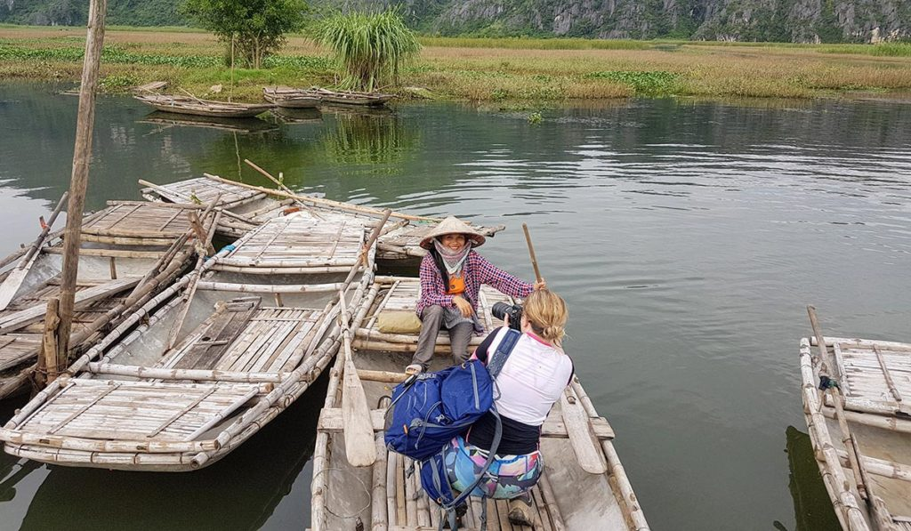Female travel photographer taking photo of local Vietnamese woman in Ninh Binh on a boat