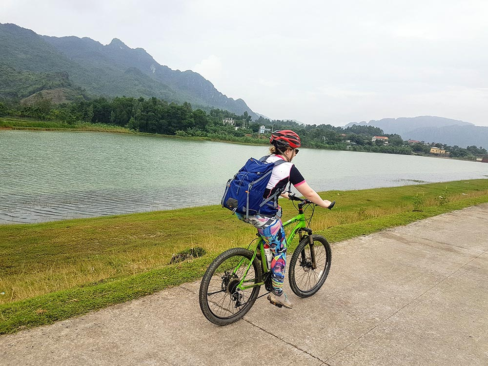 Woman cycling in Vietnam with the MindShift Gear Ultralight Dual 25L