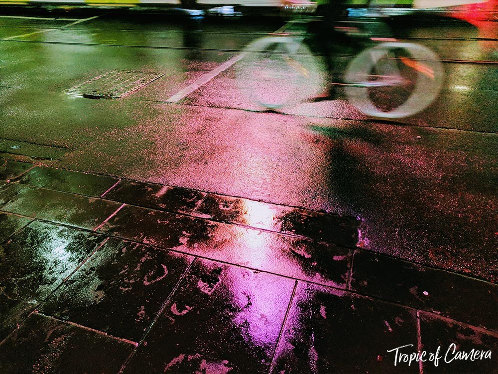 Neon reflections with a cyclist on a rainy Melbourne street