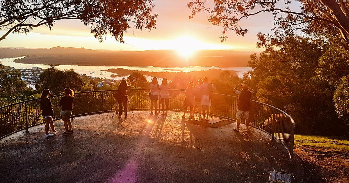 People watch the sunset at Laguna Lookout in Noosa National Park