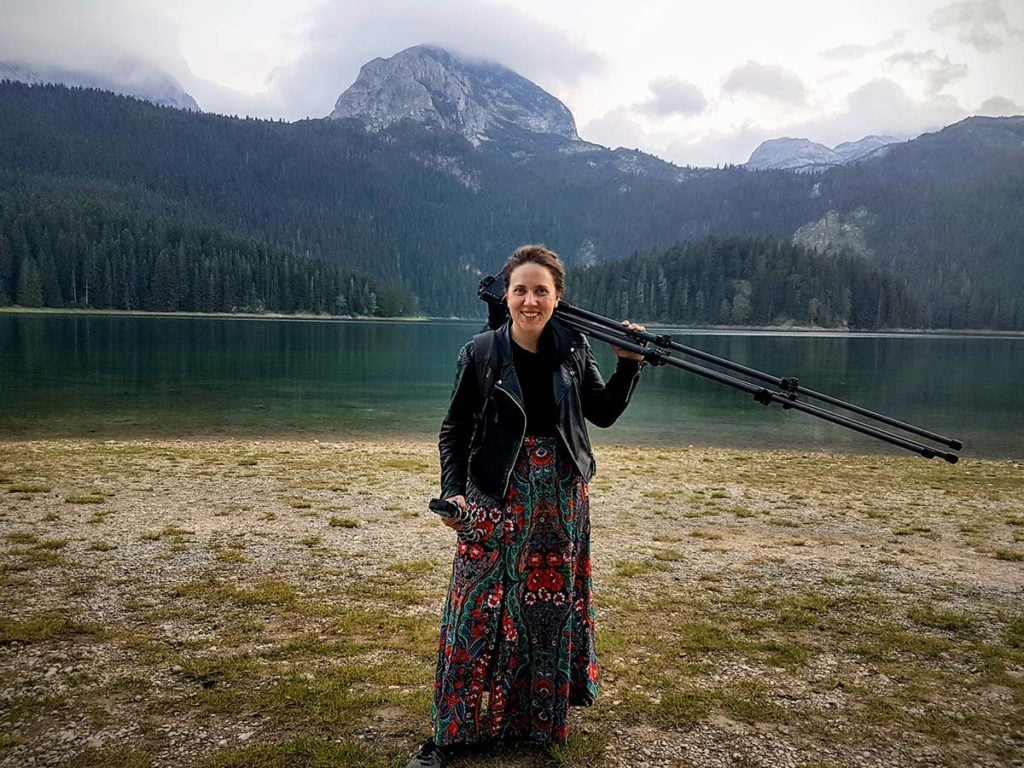 Photographer Kat Clay in Durmitor National Park carrying a camera and tripod
