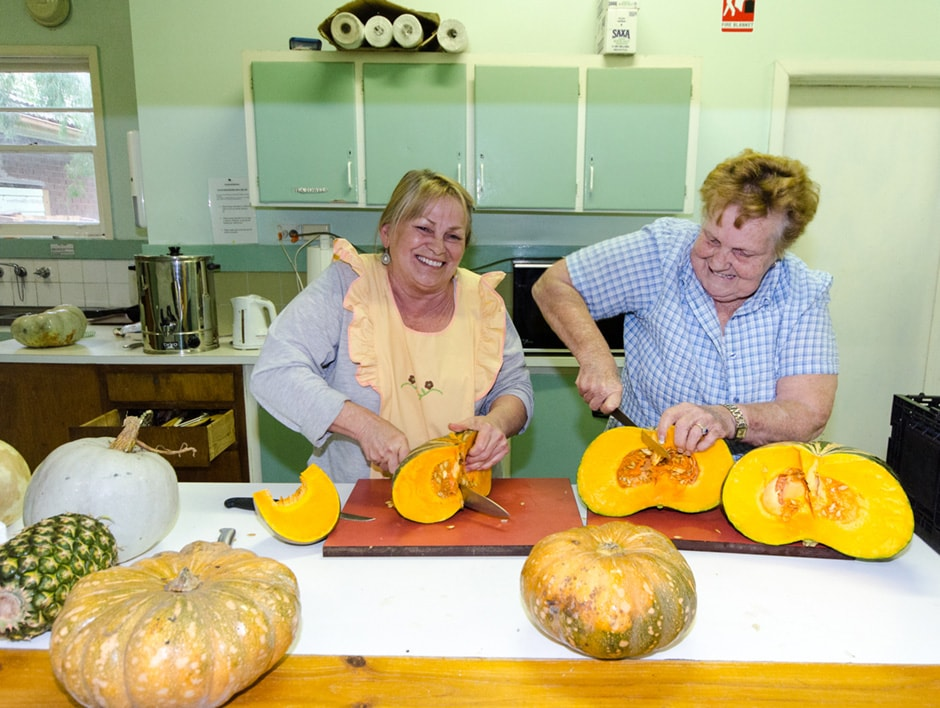 Two women cutting up pumpkin in a kitchen