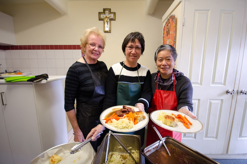 Three women providing a food service at a church