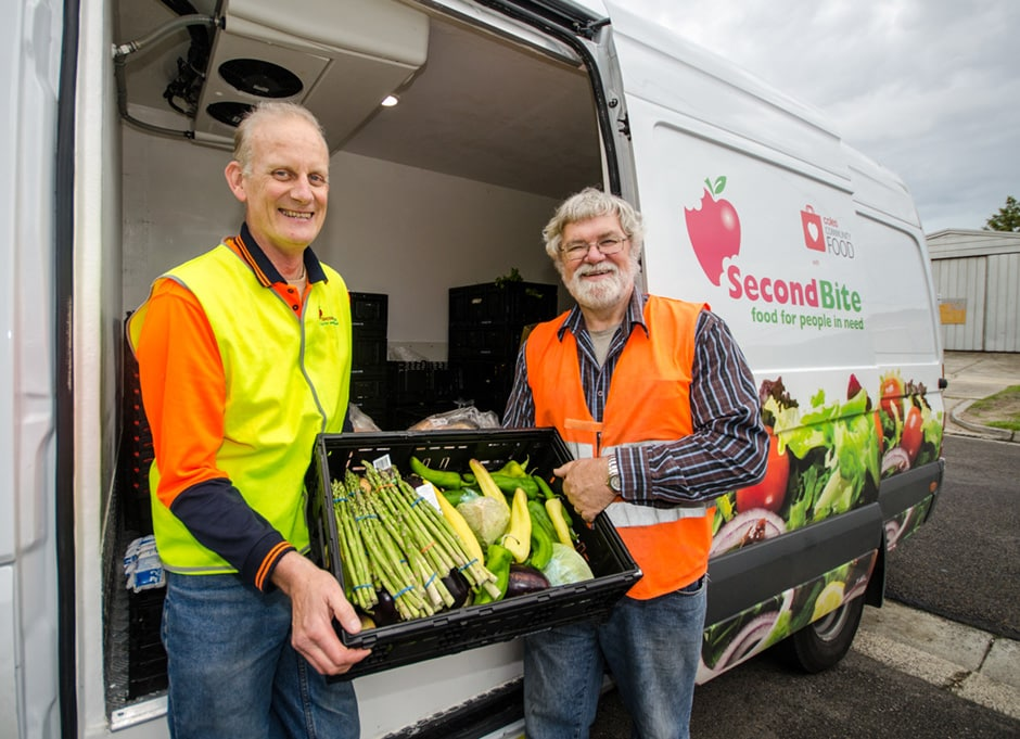 Two men delivering vegetables from a van