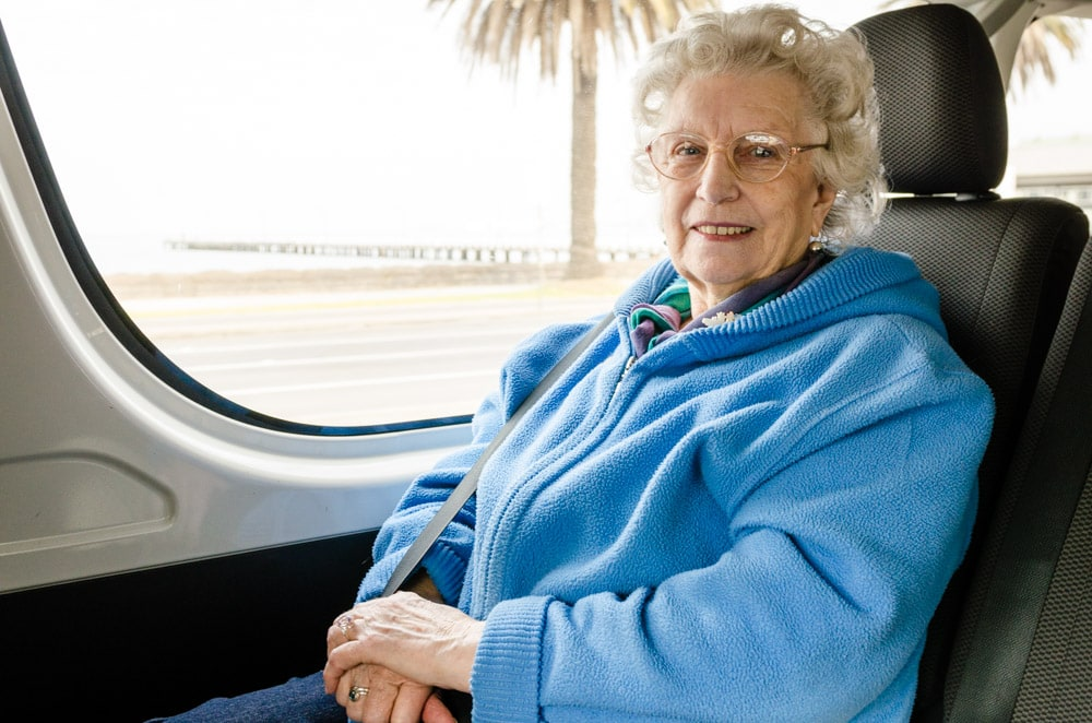 An elderly woman taking a car ride