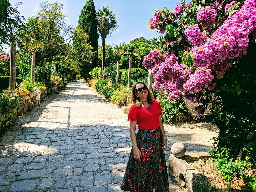 Woman standing in front of purple flowers in Trsteno Gardens, Croatia