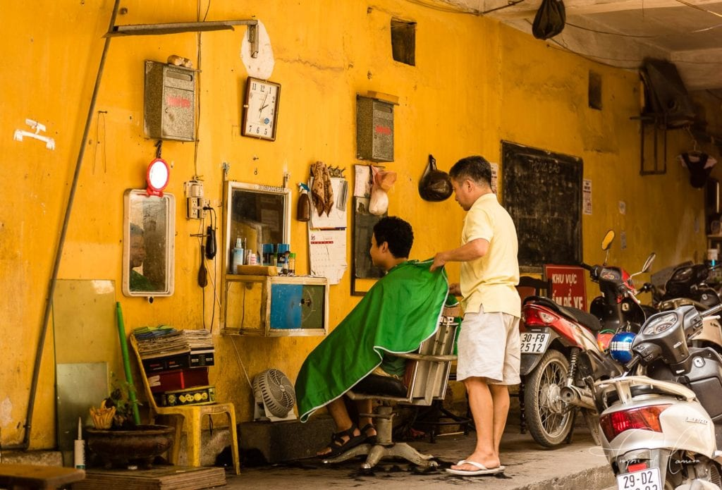 Boy getting a haircut in a colourful shop in Vietnam
